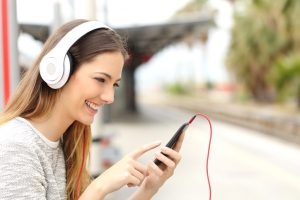 Teen girl listening to the music with headphones in a train station while she is waiting